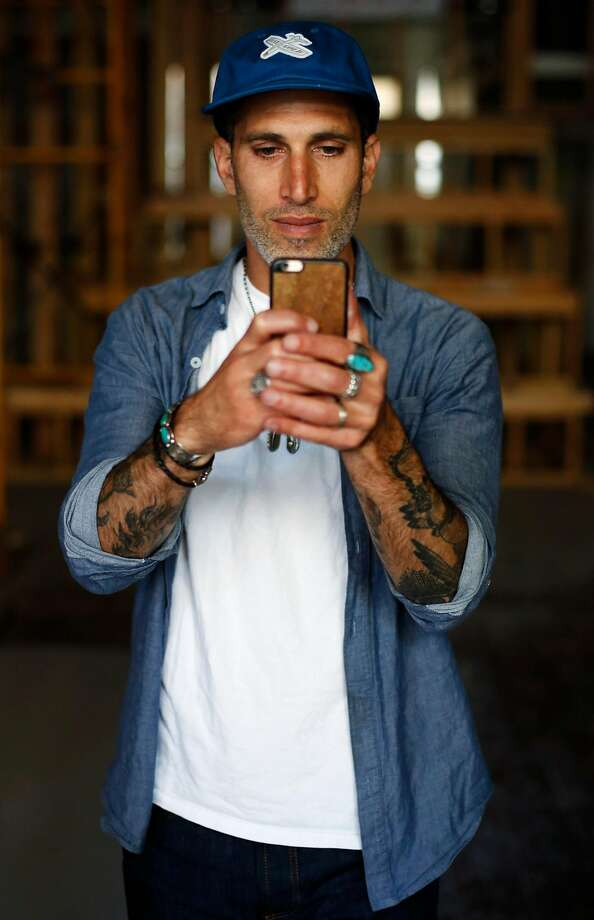 Benny Gold, founder and owner of clothing boutique Benny Gold, takes a photo with his phone in his new shop-cafe-office space under construction on Valencia Street in S.F. Photo: Connor Radnovich, The Chronicle