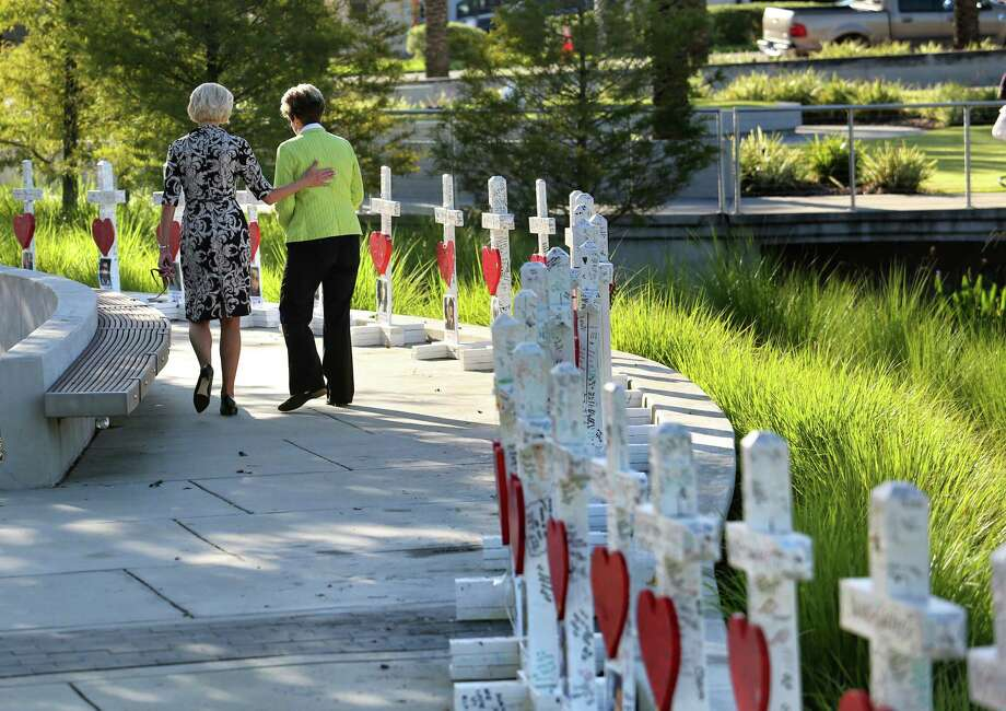 On the the one-month anniversary of the Pulse nightclub massacre in Orlando, Fla., Orlando city commissioner Patty Sheehan, right, and a friend take a last look at crosses honoring the 49 victims, before they were transferred to the Orange County Regional History Center,Tuesday, July 12, 2016. The 49 crosses were made by a Chicago carpenter to honor each of the victims killed at Pulse on June 12.  (Joe Burbank/Orlando Sentinel via AP) Photo: Joe Burbank, MBO / Orlando Sentinel