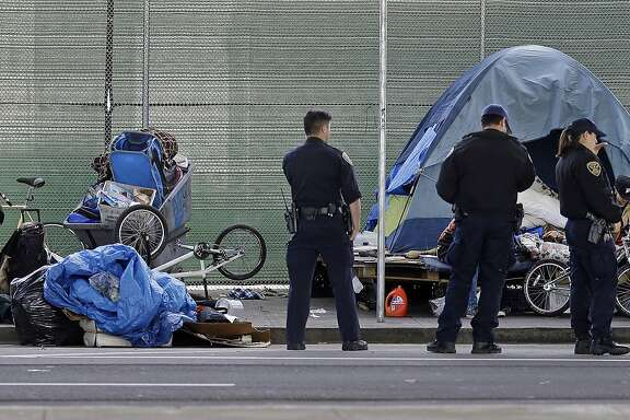 San Francisco police officers wait while homeless people collect their belongings Tuesday, March 1, 2016, in San Francisco. Crews in San Francisco have begun sweeping out a homeless camp under the city's Central Freeway that was declared a health hazard and for months has been a source of irritation for neighbors and nearby businesses. (AP Photo/Ben Margot)
