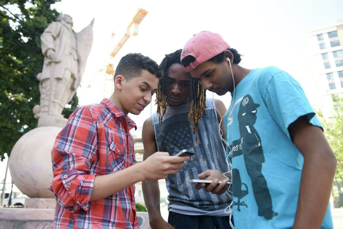 Stamford kids Keivian Guillaume, left, 15, Rashaun Lawson, center, 17, and Sam Makwana, 17, play the new Pokémon Go augmented reality mobile game at Columbus Park in Stamford, Conn. Wednesday, July 12, 2016. The new game incorporates the GPS, time and camera features on the user's phone to give the appearance that the Pokémon creatures exist in the real world.