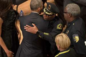 """President Barack Obama embraces Dallas Police Chief David Brown during a memorial service for the five police officers killed in Dallas on July 7, at the Morton H. Meyerson Symphony Center, July 12, 2016. Obama said Tuesday that the nation mourned along with Dallas for its five fallen police officers, but he implored Americans not to give in to despair or the fear that """"the center might not hold."""" (Stephen Crowley/The New York Times) ORG XMIT: XNYT157"""