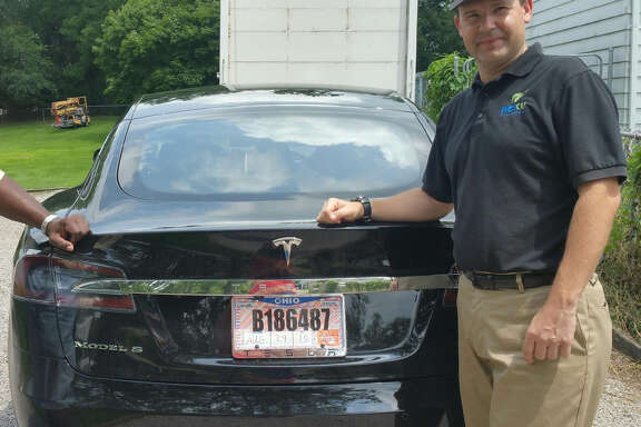 In this 2015 photo provided by one of his  neighbors,  Joshua Brown shows off his  new Tesla Model S  in Canton, Ohio.