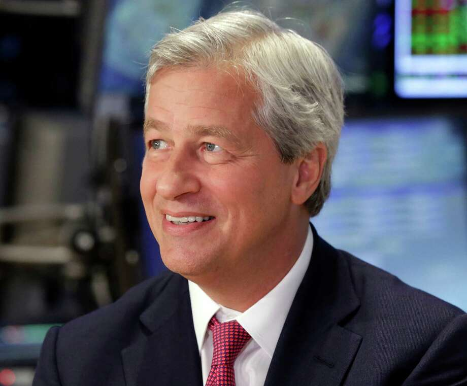 FILE - In this July 12, 2013, file photo, JPMorgan & Chase Co. Chairman and CEO Jamie Dimon is interviewed on the floor of the New York Stock Exchange. In an op-ed published Tuesday, July 12, 2016, in the New York Times, JPMorgan Chase said it will give raises to 18,000 tellers, customer service employees, and other workers over the next two years. In the op-ed, Dimon wrote that the bank will raise its minimum pay to a range of $12 to $16.50 an hour, depending on market and location factors. Its current minimum pay is $10.15 an hour. Dimon also wrote that the bank will invest more in training that helps workers get promoted to higher-paying positions. (AP Photo/Richard Drew, File) Photo: Richard Drew, STF / Copyright 2016 The Associated Press. All rights reserved. This material may not be published, broadcast, rewritten or redistribu