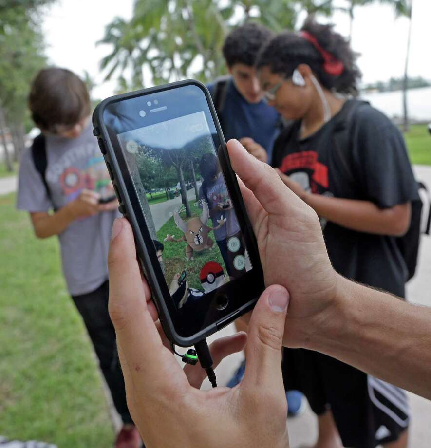 "Pinsir, a Pokemon, is found by a group of Pokemon Go players, Tuesday,  July 12, 2016, at Bayfront Park in downtown Miami. The ""Pokemon Go"" craze has sent legions of players hiking around cities and battling with ""pocket monsters"" on their smartphones. (AP Photo/Alan Diaz) Photo: Alan Diaz, STF / Copyright 2016 The Associated Press. All rights reserved. This material may not be published, broadcast, rewritten or redistribu"