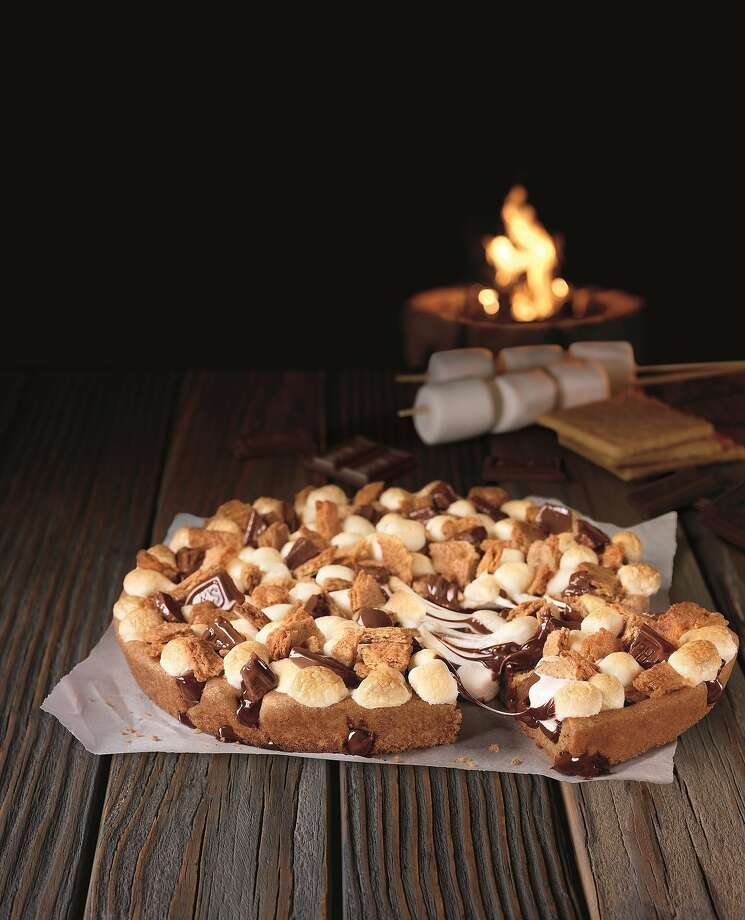 """Pizza Hut's Toasted S'mores Cookie:a freshly baked, big ol' chocolate chip cookie covered with mini marshmallows, chocolate chunks and crumbled Graham crackers. Think of this as a dessert pizza.  Total calories (for one slice of the pie): 240. Fat grams: 10. Sodium: 100 mg. Carbs: 33 g. Dietary fiber: 1 g. Protein: 3 g. Manufacturer's suggested retail price: $6.99. What Hoffman says: Someone in Pizza Hut product development is a smart cookie to think up this dessert. It starts with a humongous chocolate chip cookie - everybody loves those. Then the Hut adds the flavor and textures of s'mores - gooey marshmallows and more gooey chocolate. Good on Pizza Hut for coming up with a product that doesn't have customers wondering, """"Whaaaa?"""" Like BBQ Bacon Cheeseburger and Buffalo Chicken with Sriracha Drizzle pizzas. Seriously, Pizza Hut, what were you thinking? Click here to read Hoffman's take on the pizza."""