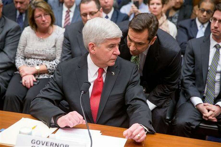 Michigan Gov. Rick Snyder speaks with a member of his staff as he arrives to testify before a House Oversight and Government Reform Committee hearing in Washington Thursday. Photo: Andrew Harnik | AP Photo