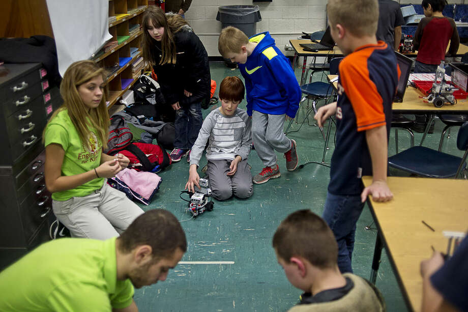 Plymouth fourth-graders Trevor Hallberg, 10, center left, and Braiden Katzinger, 10, center right, get ready to test their robot in a game of tug-of-war at Plymouth Elementary School on Tuesday. Engineering for Kids, which offers after-school and birthday party programs focused on STEM activities, will be opening a Learning Center at 324 S. Saginaw Road. There will be an open house Saturday from 3 p.m. to 8 p.m. Photo: Erin Kirkland | Midland Daily News