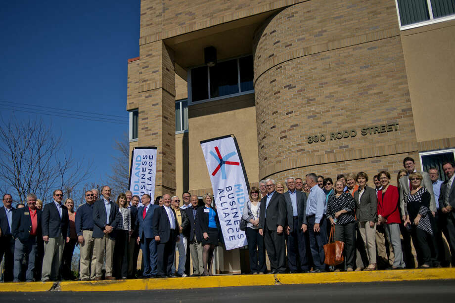 Business professionals pose outside of the Carl A. Gerstacker Commerce Center during the recent unveiling of the Midland Business Alliance. Photo: Nick King | Nking@mdn.net