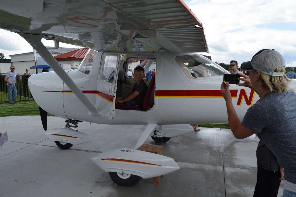 Shannon Forshee, of Midland, takes a photo of her 8-year-old son, Sam, inside a modified airplane at the dedication ceremony for the Midland Community Aviation Discovery Area at Jack Barstow Municipal Airport on Sunday.