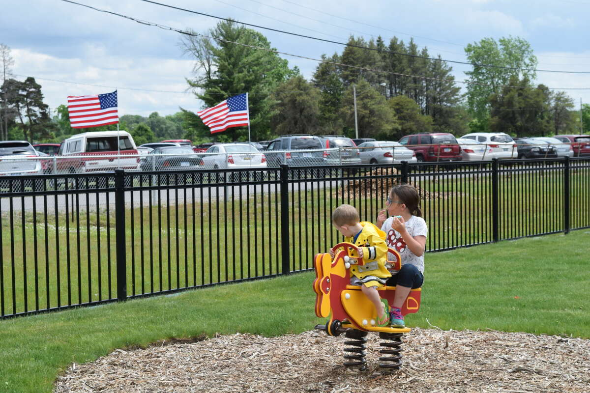 Siblings Skyler O'Laughlin, 2, and Taylen O'Laughlin, 7, right, play together at the dedication ceremony for Jack Barstow Airport's new Midland Community Aviation Discovery Area on Sunday.