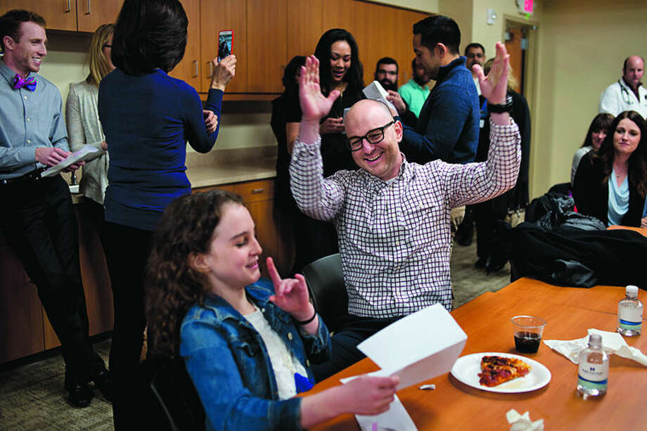 "Fourth-year Michigan State University College of Human Medicine student Seth Simpson, center, raises his hands in celebration as his daughter Ella Simpson, 10, both of Midland, announced that he matched into the triple board residency program at Cincinnati Children's Hospital Medical Center on Friday afternoon at the MidMichigan Medical Center Gerstacker Building. Simpson along with eight other Midland Regional Campus fourth-year medical students found out what residency programs they matched with. Cincinnati was Simpson's top choice where he'll do a 5 year residency focusing on pediatrics, psychiatry, and child psychiatry. ""It's awesome,"" Simpson said. ""But nerve racking to know that I'm starting my residency."" Photo: Brittney Lohmiller/Midland Daily News"
