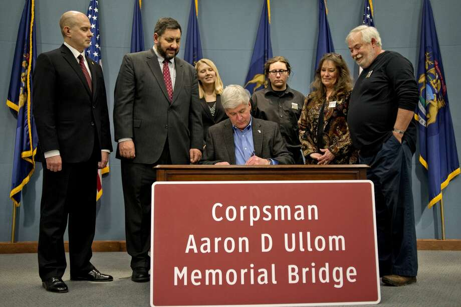 "From left, Rep. Gary Glenn, R-Midland, Sen. Jim Stamas, R-Midland, legislative aide Erinn Kane, the brother of Aaron Ullom Sean Bartley, and Debi and Kevin Ullom, Aaron's parents, watch as Gov. Rick Snyder signs Senate Bill 513 which designated the U.S. 10 bridge over Eastman Avenue in Midland as the ""Corpsman Aaron D. Ullom Memorial Bridge."""