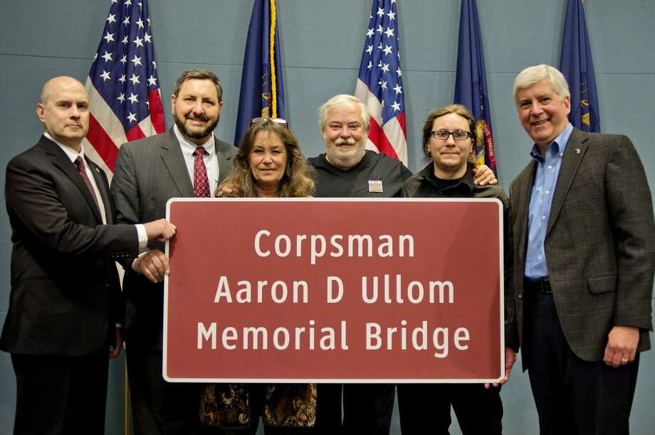"In this Daily News file photo, from left, Rep. Gary Glenn, R-Midland, Sen. Jim Stamas, R-Midland, Debi and Kevin Ullom, the parents of Aaron, Sean Bartley, Aaron's brother and Gov. Rick Snyder pose by the sign that reads ""Corpsman Aaron D. Ullom Memorial Bridge."" A ribbon-cutting ceremony is now planned on Saturday, July 9, officially dedicating a memorial bridge in Ullom's honor."