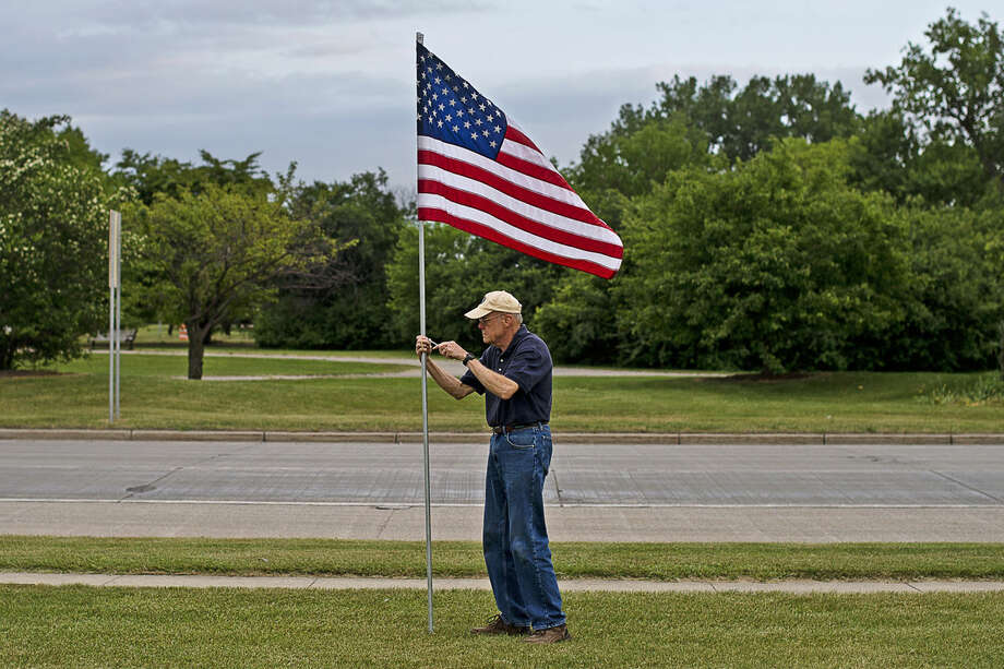 Kiwasse Kiwanis Club member Duane Townley unscrews a flag before the sun sets on Tuesday off East Patrick Road. Photo: Erin Kirkland | Midland Daily News