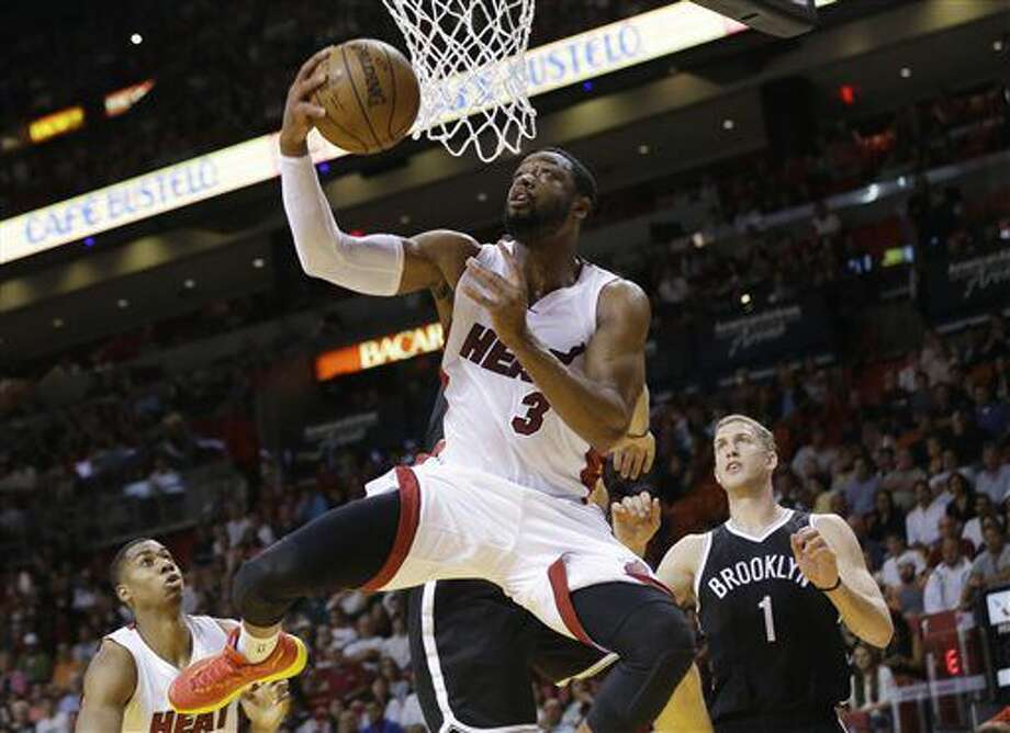 FILE - In this Jan. 4, 2015, file photo, Miami Heat guard Dwyane Wade (3) shoots in front of Brooklyn Nets center Mason Plumlee (1) during the first half of an NBA basketball game in Miami. Wade has been extended a two-year, $40 million contract offer to stay with the Miami Heat, a person with knowledge of the negotiations told The Associated Press on Monday, July 4, 2016. (AP Photo/Lynne Sladky, File) Photo: Lynne Sladky