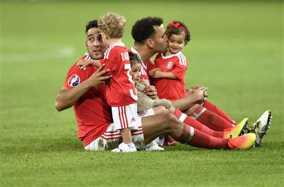 Wales' James Chester, left, and Wales' Hal Robson Kanu play with their children on the pitch at the end of the Euro 2016 quarterfinal soccer match between Wales and Belgium, at the Pierre Mauroy stadium in Villeneuve d'Ascq, near Lille, France, Friday, July 1, 2016. Wales won 3-1. (AP Photo/Martin Meissner) Photo: Martin Meissner