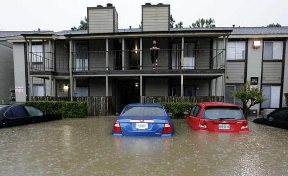 A resident looks out from the second floor as floodwaters surround his apartment complex Monday, April 18, 2016, in Houston. Storms have dumped more than a foot of rain in the Houston area, flooding dozens of neighborhoods and forcing the closure of city offices and the suspension of public transit. (AP Photo/David J. Phillip) Photo: David J. Phillip