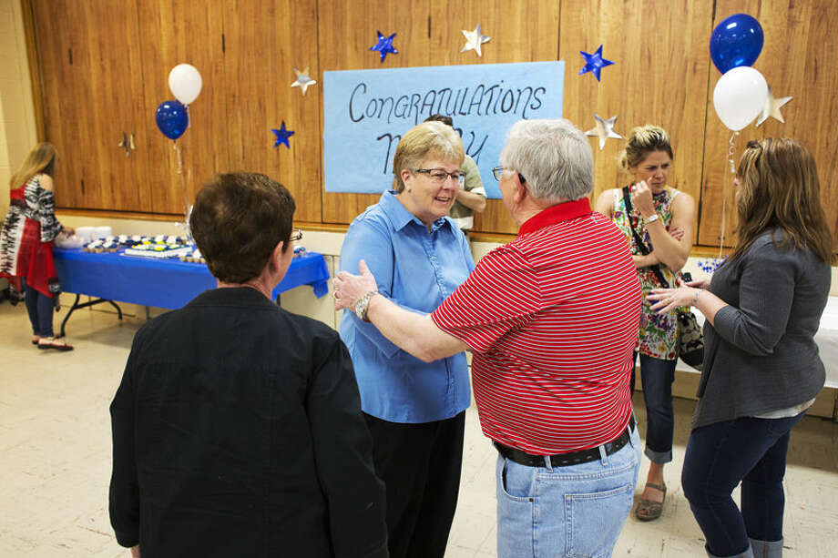 Mary Pitchford, CHS Superintendent, center, shakes hands before receiving a hug from Bob Clarke, originally from Coleman now Midland, right, and his wife Jo Clarke, left, during a retirement party for Pitchford at the Greater Midland Coleman Family Center on Friday. Clarke retired as a teacher from the Coleman School district before moving to Midland. Photo: THEOPHIL SYSLO | For The Daily News