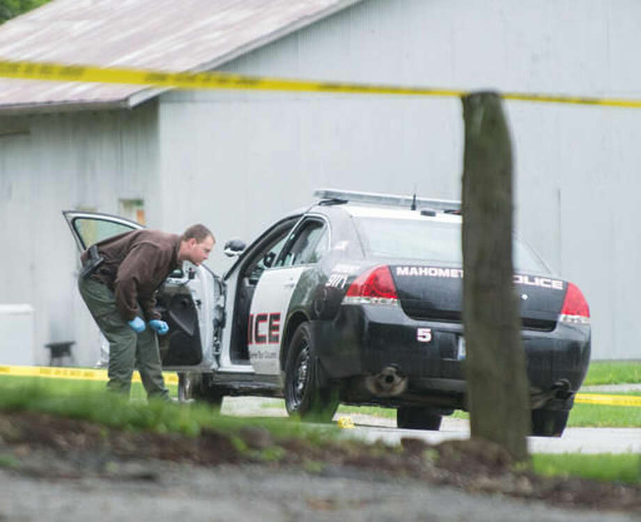 "An Illinois State Police crime scene technician processes the scene where a Mahomet police officer was shot, in the 500 block of South Vine, in Mahomet, Ill.  A manhunt for Dracy ""Clint"" Pendleton ended with the suspect being shot and killed by police. Photo: John Dixon 
