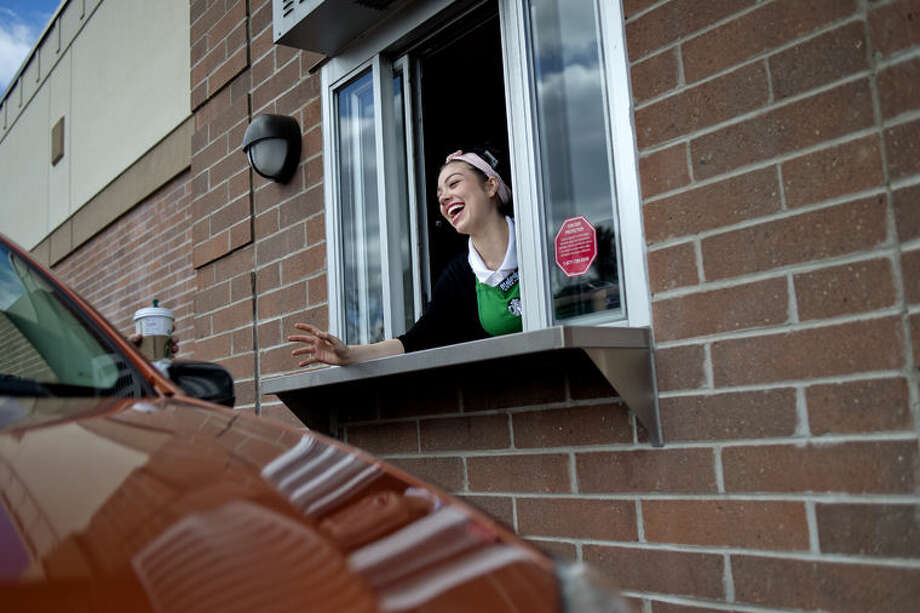 """Starbucks employee Melody Robbins jokes with a customer after giving him coffee from the drive-through window at the Midland location. Starbucks is a common place where patrons """"pay it forward"""" by paying for other customer's coffee. Photo: Nick King/Midland Daily News"""