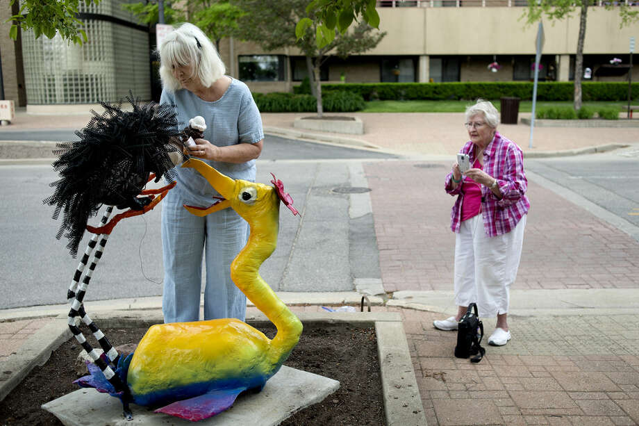 "Alice Strack, right, watches as Sally Allan, left, puts the finishing touches on their sculpture ""Prickly Pair."" ""This is our joint adventure in mischief,"" Strack said. Nine different sculptures are a part of the this year's summer sculpture series, ""Whimsy."" Photo: Brittney Lohmiller 