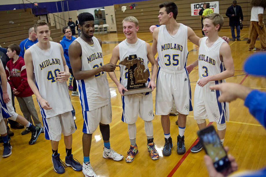 Midland seniors are shown with the regional title trophy after the Chemics beat the Saginaw Trojans 60-56. Unranked Midland (17-6) and second-ranked Dakota (25-0) will meet in the Class A quarterfinals at Grand Blanc High School on Tuesday at 7 p.m. Photo: Erin Kirkland | Midland Daily News