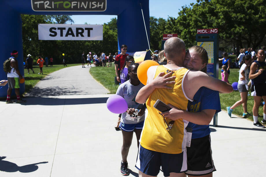 Jeremy Smith, director of Cross Country/Track & Field at Spring Arbor University, embraces Midland High School freshman Payton Stearns after crossing the finish line during a 5K in memory of Quinten Greiner on Sunday.  Greiner, 20, a Midland High 2014 graduate, was a track and cross country star and student athlete at Spring Arbor University. His dad is a pastor at Eagle Ridge Church of God. Greiner was killed in a car accident last week on his way to the airport to work as a counselor at Warner Camp, a Christian camp, for the summer. His friend, Brad Belson, organized the 5K to commemorate Quinten. Photo: Theophil Syslo | For The Daily News