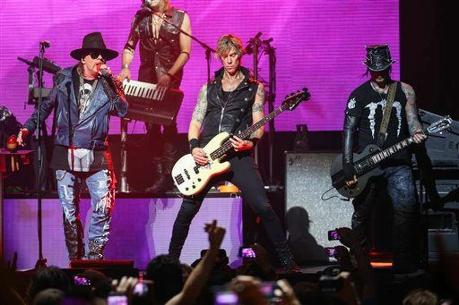 FILE - In this April 23, 2014 file photo, Axl Rose, from left, Duff McKagan and DJ Ashba of Guns N' Roses perform on stage at the 6th Annual Revolver Golden Gods Award Show at Club Nokia in Los Angeles. Crowds thronged for tickets after a surprise announcement that Guns N' Roses would play a concert Friday night, April 1, 2016, at West Hollywood's famed Troubadour music venue. The band announced on its website and in a press release that a limited number of tickets at a very old-school price of $10 apiece would be available at noon at the former location of the famous Tower Records store on the Sunset Strip. (Photo by Paul A. Hebert/Invision/AP, File) Photo: Paul A. Hebert
