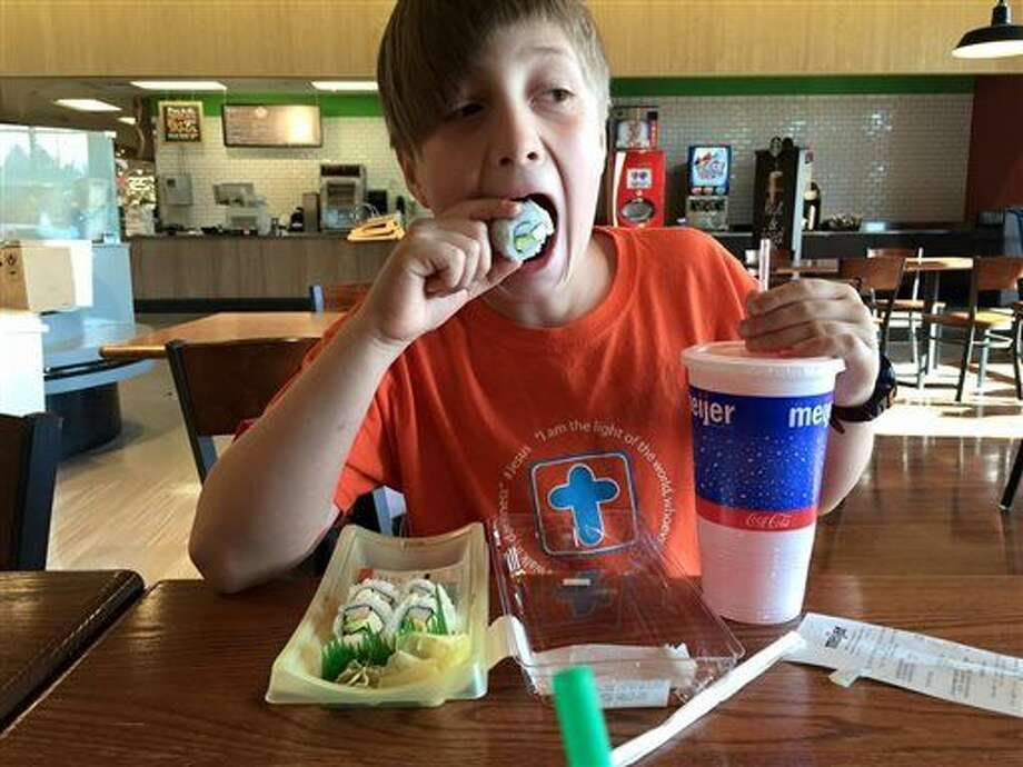 In this Saturday, April 16, 2016 photo provided by Kristen Moore, her son Fletcher Moore eats sushi at a Meijer store in Grand Rapids, Mich. The 9-year-old had a party and spent nine hours at the store to celebrate his birthday. (Kristen Moore via AP) Photo: Kristen Moore