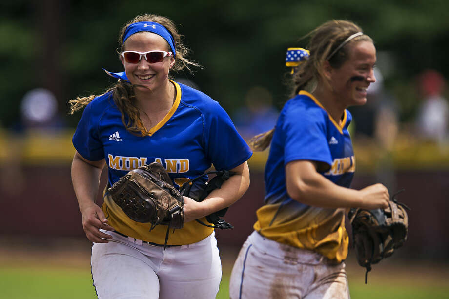 ERIN KIRKLAND | ekirkland@mdn.net Midland's Maya Kipfmiller, left, and Tara Gross, right, smile while returning to the dugout between innings on Tuesday during the Division 1 softball state quarterfinal at Central Michigan University. The Chemics beat the Rams 8-1. Photo: Erin Kirkland/Midland Daily News