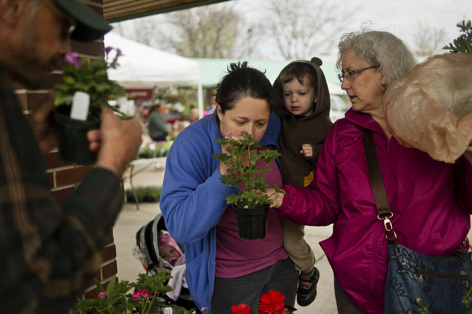 From left, Mt. Hope Herb Farm owner Jim Swinson smells plants as customers and Midland residents Emily Goodell, center, son Samuel Goodell, 2, and Goodell's mother Peggy Hoff, right, check out items at the Midland Area Farmers Market in this 2016 file photo. Mt. Hope Herb Farm returns to the market this year. Photo: Erin Kirkland | Midland Daily News