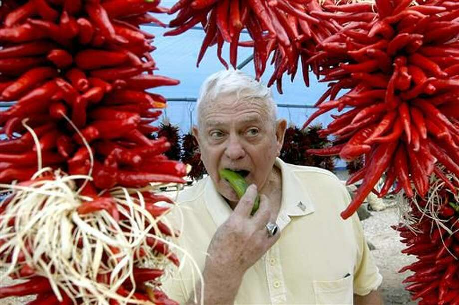 FILE - In this Aug. 30, 2008 file photo, framed by ristras, John Trewitt bites into a pod of fresh Hatch green chile, at the Hatch Chile Festival in Hatch, N.M. A federal appeals court is siding with an association of green chile growers in the Hatch Valley of southern New Mexico in a dispute over what food can be fairly labeled with the renowned Hatch name. The U.S. 10th Circuit Court of Appeals on Friday, June 17, 2016, ruled in favor of the Hatch Chile Association and allied Albuquerque food distributor El Encanto in their efforts to subpoena records that may indicate whether a rival's products contain purely Hatch-grown chile as marketing suggests. Photo: Norm Dettlaff/The Las Cruces Sun-News Via AP, File