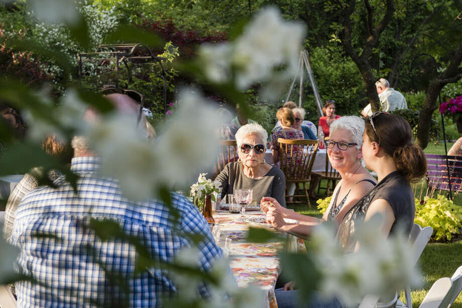 Neighborhood residents Doris Feagley, Cathy Richard and Jessica Martin chat during the Richards' annual mock orange blossom party on Friday, June 10. The tables are set up near the mock orange shrubs so guests can enjoy their sweet citrus scent. Photo: Danielle McGrew Tenbusch