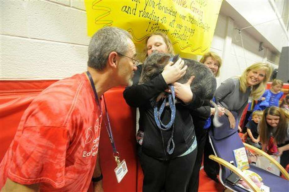 """Science/media specialist Terry Schneider kisses """"Dillon,"""" a one year-old pig, after students read 5,500 books at Alameda Early Childhood Preschool in Farmington Hills. Photo: Steve Perez 