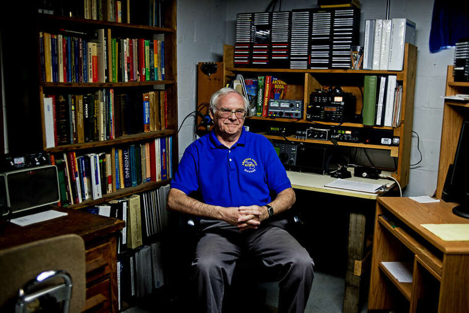 Amateur radio operator Lee Hodges poses for a portrait surrounded by his radio equipment at his Midland home on Tuesday. Hodges has been involved in amateur radio since 1997. Photo: ERIN KIRKLAND | Ekirkland@mdn.net