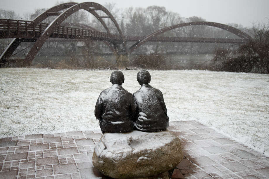 During the height of the storm on Wednesday afternoon, snow could be seen collecting on The Couple statue inChippewassee Park near the Tridge. Photo: Brittney Lohmiller | Midland Daily News