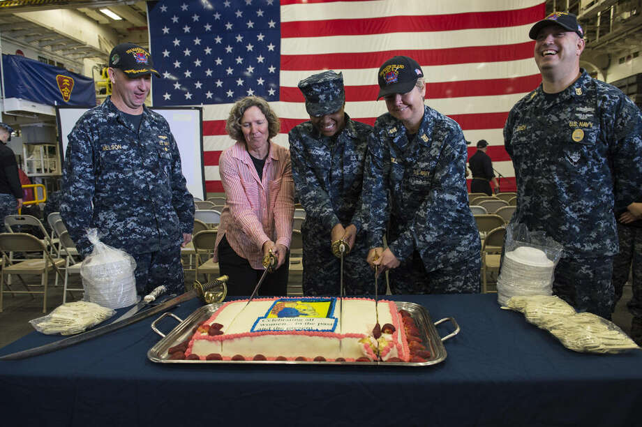SAN DIEGO (Mar. 22, 2016) - (Left to right) USS Makin Island (LHD 8) Executive Officer Mark Melson, Command Master Chief (Retired) Kathleen Hansen, from Midland, Michigan, Airman Zakiya Calloway, from Bainbridge, Georgia, Master Chief Avionics Maintenance Technician Joy McGill from Alloway, New Jersey, and Command Master Chief Larry Lynch cut a cake during the Women's History Month Observance in the ship's hangar bay. The event is part of a month-long women's history celebration aboard Makin Island. (U.S. Navy Photo by Mass Communication Specialist Seaman Eric Zeak/Released) Photo: Mass Communication Specialist Seaman Eric Zeak
