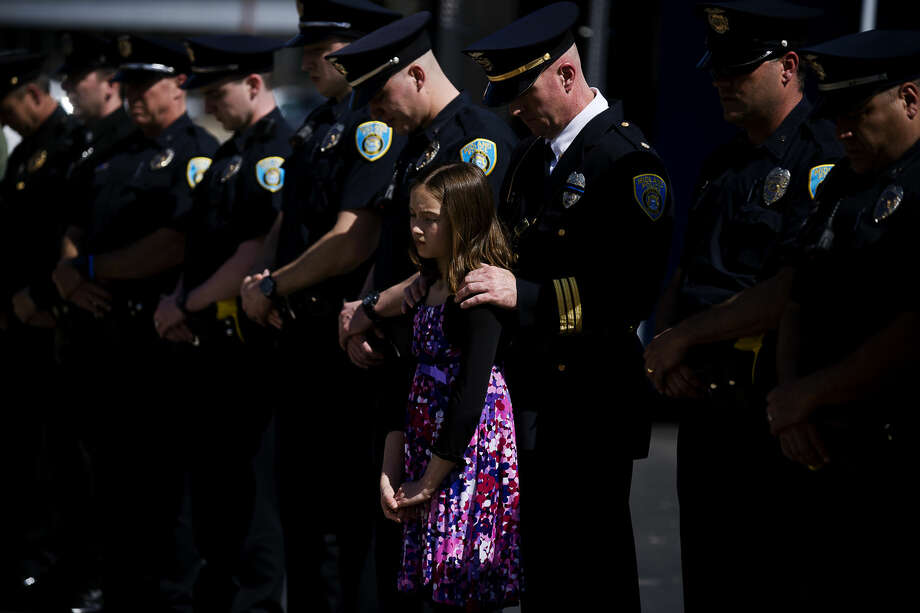 ERIN KIRKLAND | ekirkland@mdn.net Midland Deputy Police Chief Rod Roten and his daughter Brooklyn Roten, 10, bow their heads during the closing prayer at a ceremony honoring National Peace Officers Memorial Day on Wednesday at the Law Enforcement Center. Photo: Erin Kirkland/Midland Daily News
