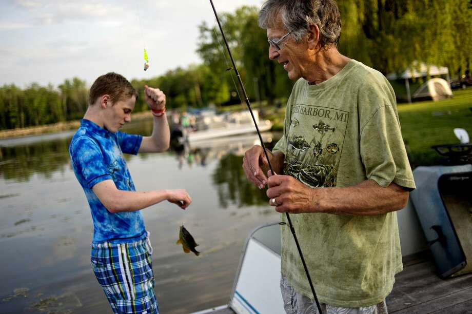 NICK KING | nking@mdn.net Larry Haines, right, holds the fishing pole for his grandson Noah, 14, as he removes the hook from the mouth of a bluegill fish he caught while fishing at his grandpa's home on Sanford Lake recently. Noah, his sister Kivrin, 12, and brother Levi, 9, spend a lot of time with their grandfather outdoors and enjoy swimming, kayaking and skiing with him. Photo: Nick King/Midland Daily News