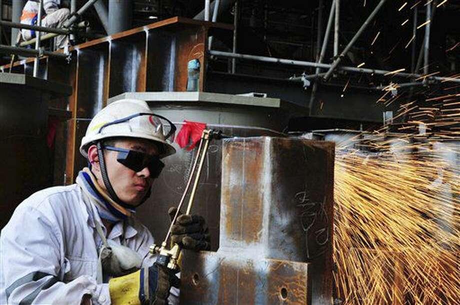 Esta foto tomada el 1 de junio del 2016 muestra a un trabajador cortando acero para una plataforma de gas natural en una subsidiaria de China Offshore Oil Engineering Co. Ltd., en Qingdao, en la provincia oriental de Shandong, en China. La manufactura china se deterioró de nuevo el mes pasado, de acuerdo con estudios divulgados el viernes 1 de julio del 2016, indicando más debilidades en la segunda economía del mundo, mientras pasa por una prolongada desaceleración. (Chinatopix via AP) CHINA OUT Photo: Uncredited