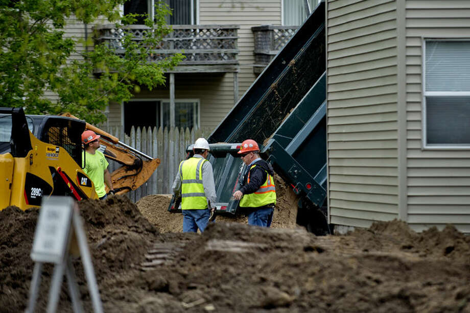 In this Daily News file photo, a crew works to spread new soil on the lot of a home in Midland. Photo: Nick King | Midland Daily News