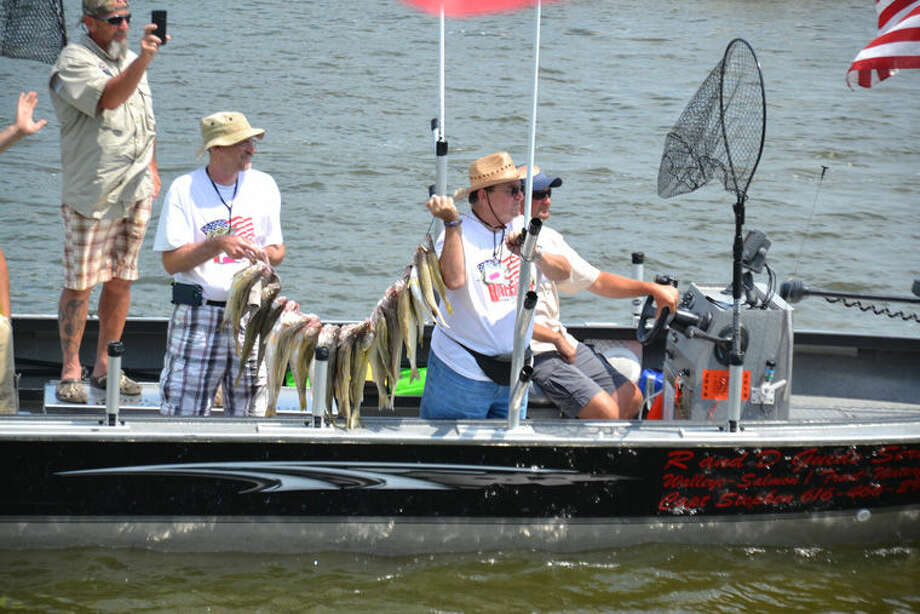Returning veterans and their hosts show off their catch during the Walleyes for Warriors event on Sunday. The event, which saw its sixth run Sunday, brought about 250 veterans out to fish for walleyes. Photo: Steve Griffin | For The Daily News