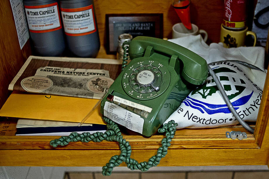 An old office phone and a sweatshirt are just a couple of items found in the Chippewa Nature Center's time capsule on Thursday. The center buried the capsule 25 years ago with the intention of it being opened for the organization's 50th anniversary. Photo: ERIN KIRKLAND | Ekirkland@mdn.net