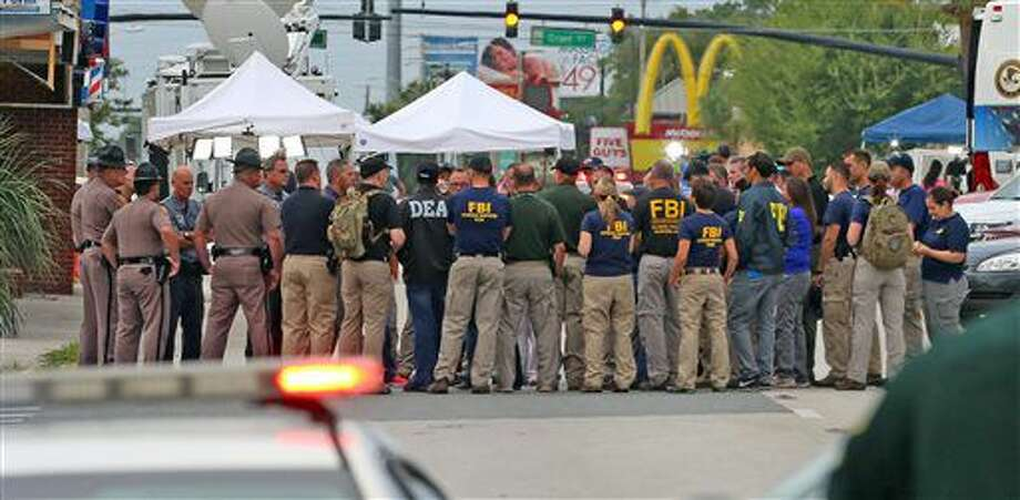 Multiple law enforcement agencies gather early Monday in front of Pulse Nightclub at the mass shooting scene in Orlando. Photo: Red Huber | Orlando Sentinel Via AP