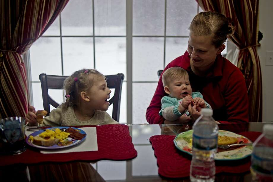 ERIN KIRKLAND | ekirkland@mdn.net Calah Blevons, 4, smiles at baby sister Saleh Blevons, 8 months, and mother Amber Blevons during dinner on Wednesday in Sanford. Blevons was born healthy but later became ill with mono encephalitis. It has left her with spasticity of the legs, a weak left arm and slow speech. She has been in physical, occupational and speech therapy for three years and is continuing to improve. Her family recently made a GoFundMe page to help raise the money to pay for hyperbaric oxygen therapy, as well as further physical therapy, with the hopes that she will be able to walk again. Photo: Erin Kirkland