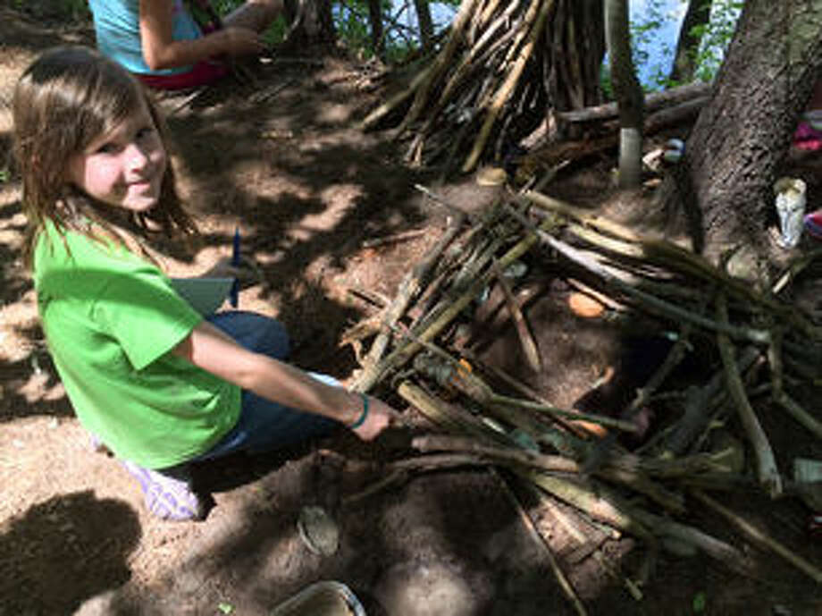 A Nature Day Camp participant builds a project next to the riverbank at the Chippewa Nature Center. For as long as the Chippewa Nature Center has been operating, its Nature Day Camp has also been sparking an interest in the great outdoors.  Photo: Photo Provided By CNC
