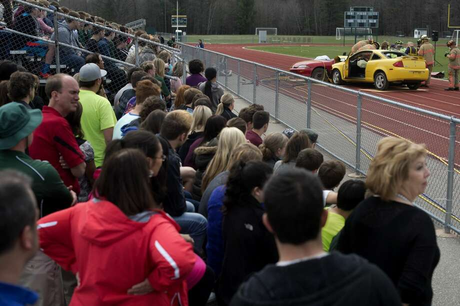 H.H. Dow High School students watch Midland firefighters use the jaws of life on a car during a simulation of a drunk driving accident at the school on Wednesday. The simulation was held by S.K.I.D., Stop Kids Impaired Driving, which is a traffic safety and underage drinking prevention program. The program shows what would happen in a real life accident for high school audiences. Photo: Brittney Lohmiller/Midland Daily News
