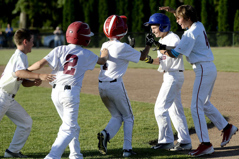 NICK KING | nking@mdn.net Wilson Miller's Caden Chritz, fourth from left, celebrates with teammates after driving in the winning run during the sixth inning on Monday at Northeast Little League's Wilson Field. Wilson Miller won the city Little League Baseball city championship 4-3. Photo: Nick King/Midland Daily News