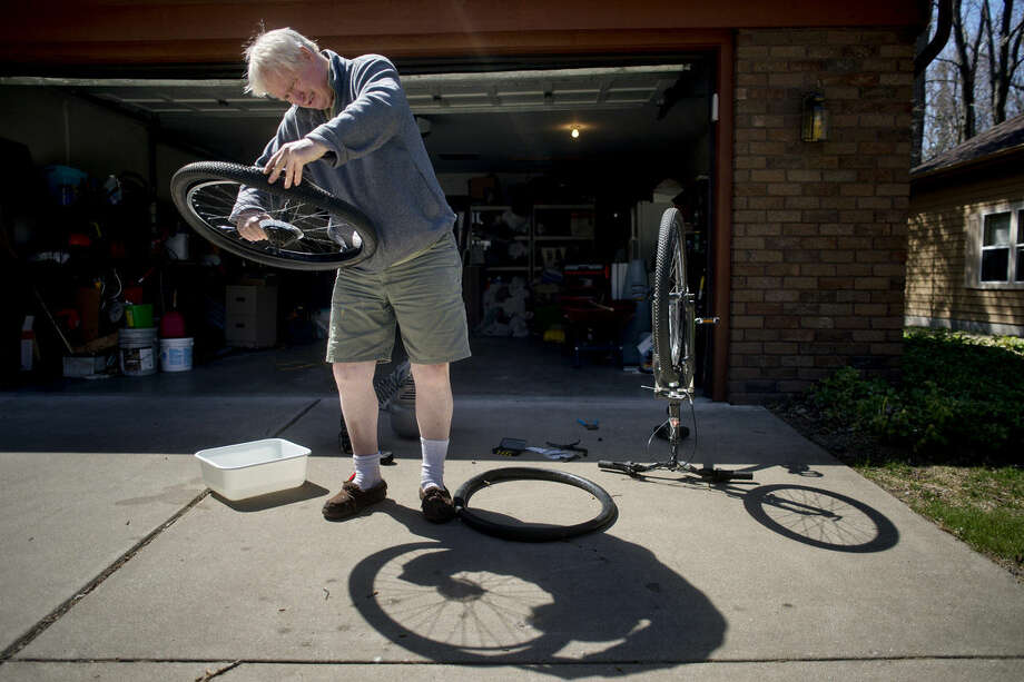 Kevin Brown of Midland looks for a hole in the inner tube of his bicycle on Tuesday afternoon. Photo: Brittney Lohmiller | Midland Daily News