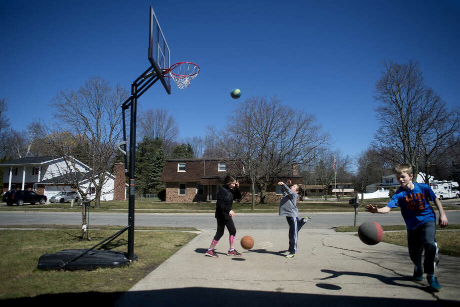 Nine-year-old Sophie Larsen, left, shoots hoops with her brothers, Daniel Larsen, 7, and Ben Larsen, 11, outside their house in Midland on Tuesday afternoon. Photo: Brittney Lohmiller | Midland Daily News